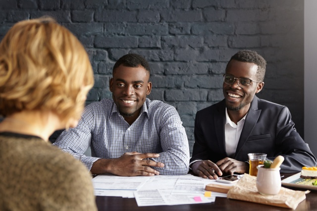 Happy African-American CEO and HR director smiling cheerfully during job interview with attractive Caucasian woman, ready to hire her to their company. People, business and communication concept
