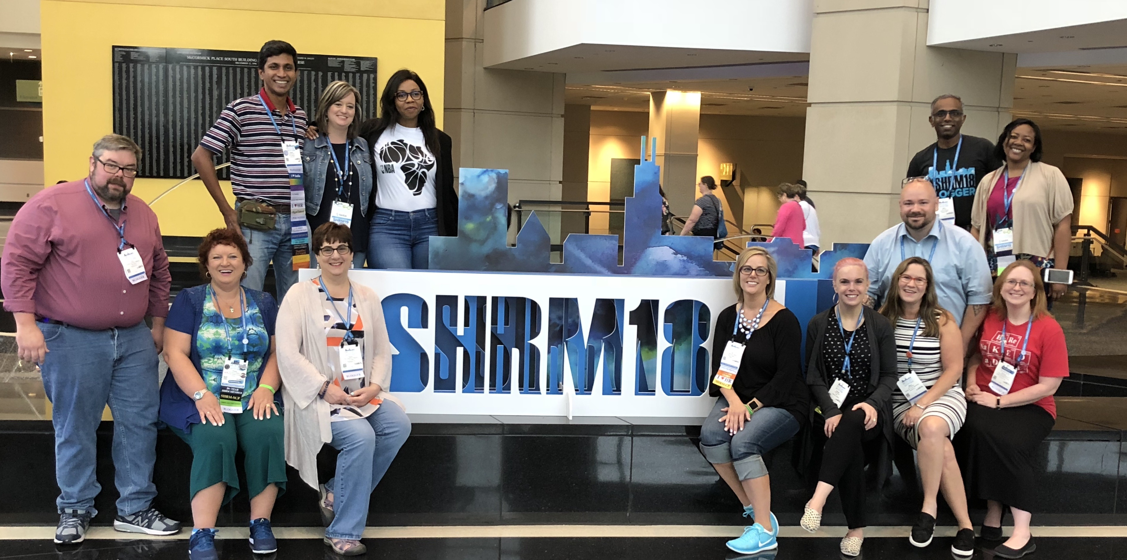 Row 1: Jon Thurmond, Paula Harvey, Anne Tomkinson, Kyra Matkovitch, Renee Robson, Mary Williams, Wendy Dailey. Row 2: Anish Aravind, Michelle Kolhoff, Mofota Sefali, Keith Enochs, Kavi, Jazmine Wilkes stand around the SHRM18 sign